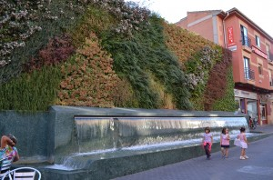 A beautiful brick wall covered in different greenery, one of many fountains, and little girls!